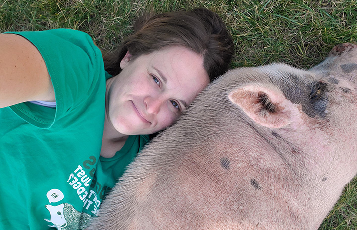 Jennifer and Diesel the pig lying with their heads next to each other on the grass
