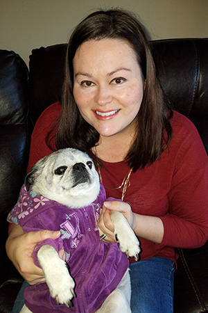Brandy Rocchio holding Piper the pug, who is wearing a purple outfit