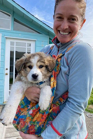 Smiling person holding fluffy puppy Maggie