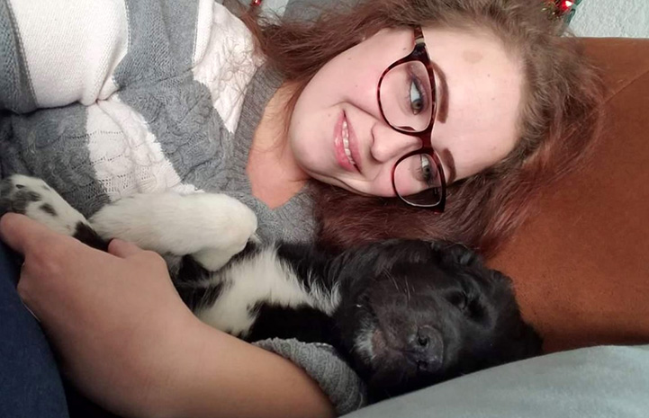 Woman lying down and snuggling with Reilly the puppy