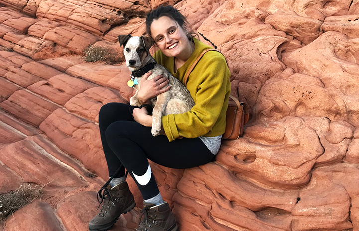 Loka the puppy being held by Elise on a red rock formation