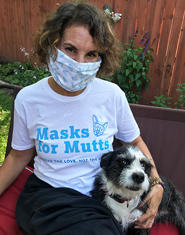Sarah Pai wearing a mask and a Masks for Mutts T-shirt sitting next to a dog