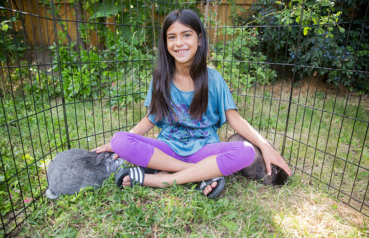 A smiling Siddha Campbell with adopted rabbits Flora and Fauna