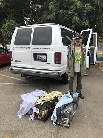 Michael with some sheet-covered live traps and a van