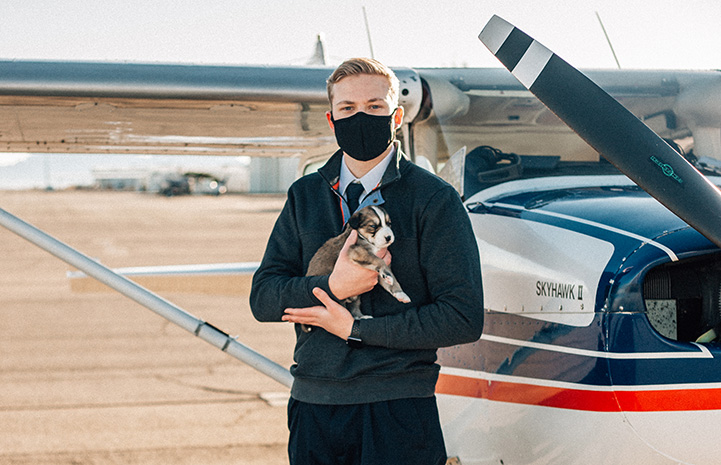 Cody Anderson holding a puppy in front of a plane