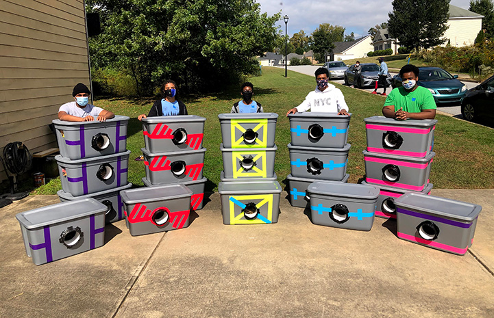 Tyrell Cooper and his Boy Scout Troop posing with the cat shelters they made and donated