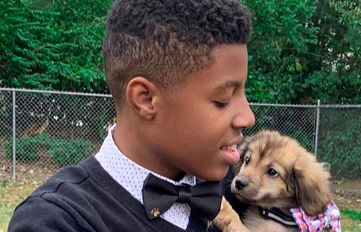 Sir Darius Brown wearing one of his bow ties and holding a small brown puppy, who is also wearing a bow tie