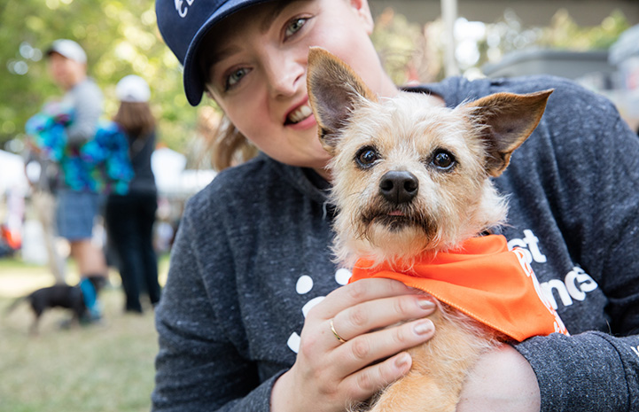 Lauren Ash wearing a long-sleeved Best Friends shirt and holding a small fluffy dog who is wearing an orange bandanna
