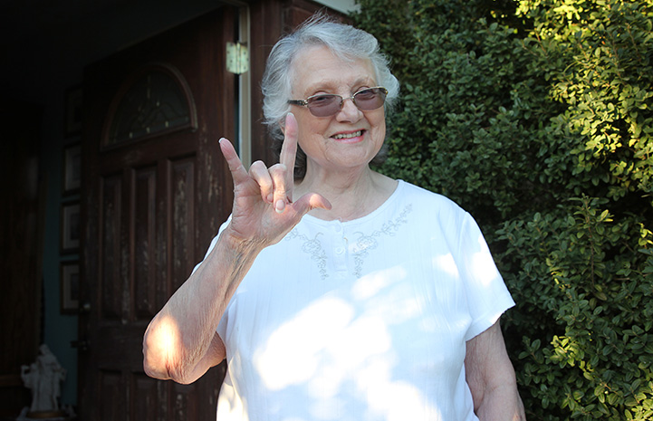Marilyn giving the hand sign for I Love You
