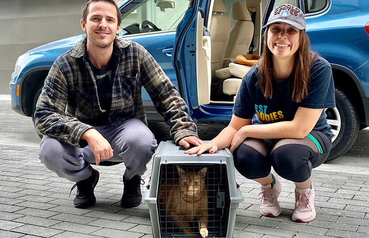 Ellie and Dave with May the cat in a kennel, who they adopted