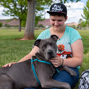 Young woman wearing a baseball hat with a gray pit bull terrier type dog