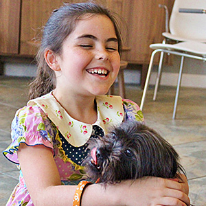 Young girl smiling and holding small furry black dog