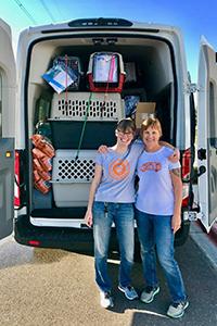 Heidi Losleben and Linda Blauch in front of the transport van