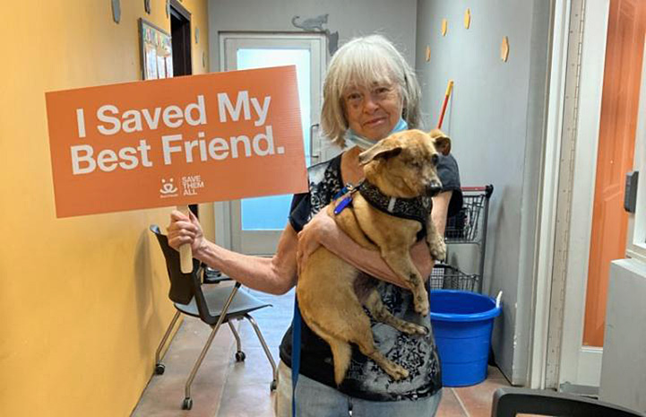Lorraine adopting Minx the dog and holding a sign that says, I Save My Best Friend