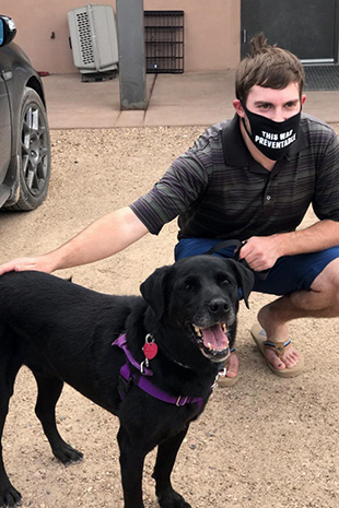 Eric wearing a mask and squatting next to Kenya the dog who is standing with a smile on her face