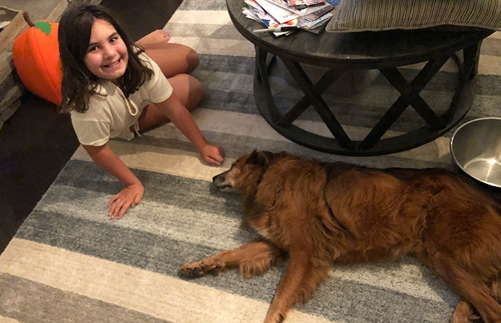 Young girl lying on the floor next to Tate the dog