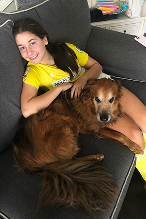 Girl wearing a sports outfit sitting on the couch with Tate the dog