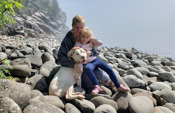 Doc the dog on a rocky beach with a woman and child