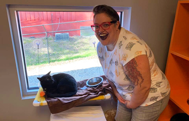 A smiling woman, Treah-Caldwell, next to a black cat next to a window