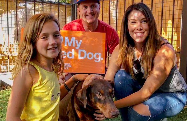 Hannah the doberman with the Kocicka family holding a sign
