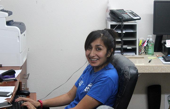 Yessy Banda sitting at a desk at Palm Valley Animal Center (PVAC)