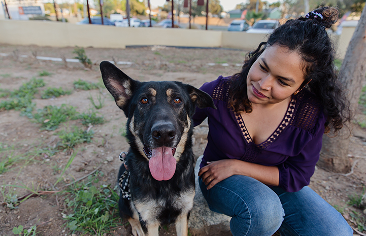 Smiling woman looking at a German shepherd with his tongue out