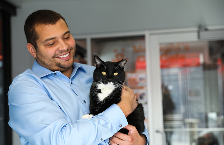 Smiling man holding a black and white cat