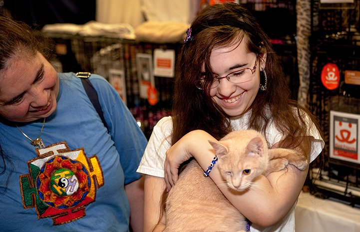 Smiling girl holding a buff-colored one-eyed cat at the New York Super Adoption