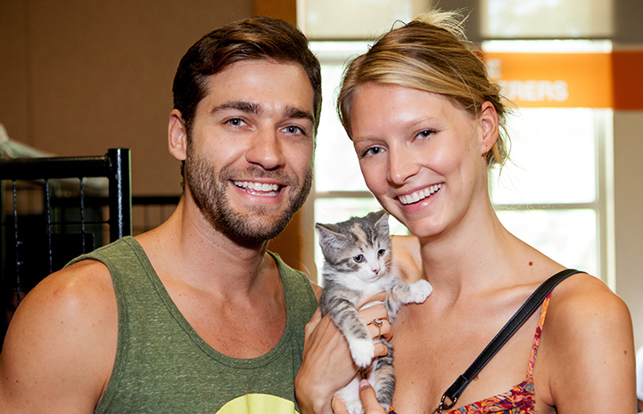Young man and woman smiling and holding a calico kitten who they adopted at the New York Super Adoption