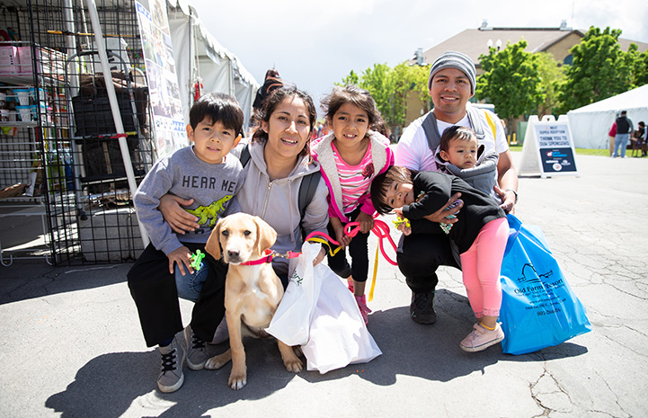 Young family adopting a yellow Lab mix puppy at the NKUT Super Adoption
