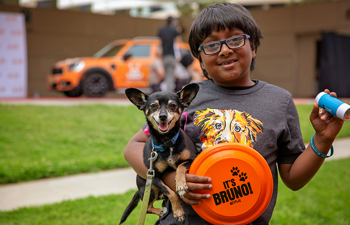 Young boy holding a small black and tan Chihuahua mix and an orange frisbee