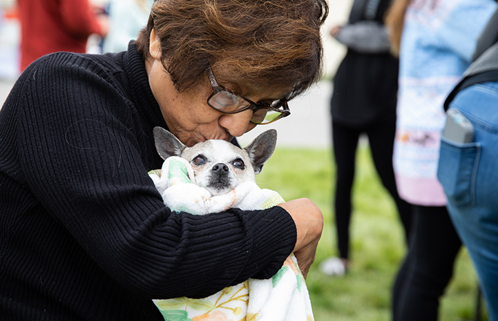 Woman kissing and hugging a small dog at the NKUT Super Adoption event