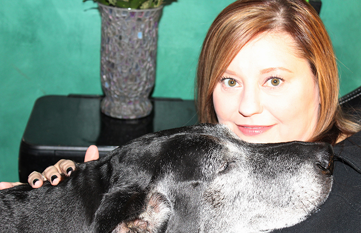 Volunteer Laura Rozler posing with a black dog with a graying muzzle