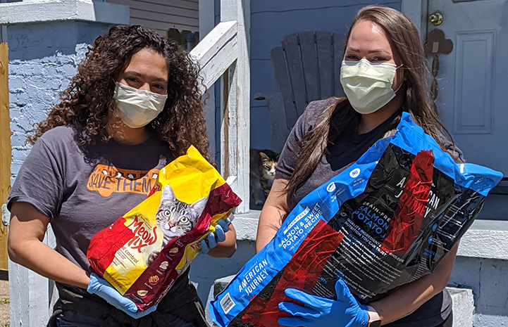 Two gloved and masked women holding large bags of pet food