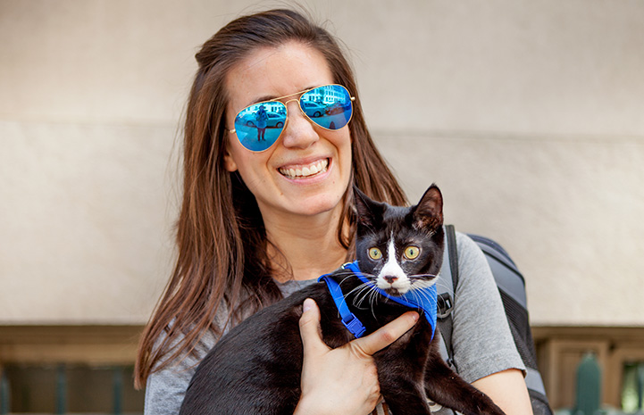 Woman wearing sunglasses holding Candycane the kitten, who is wearing a blue harness