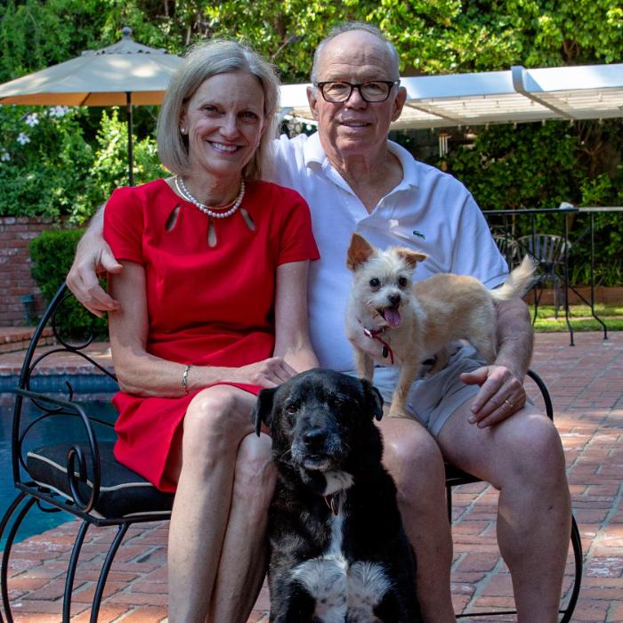 Older couple holding small dog on lap