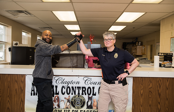"Sterling ""Trap King"" Davis holding hands up with a woman animal control officer"