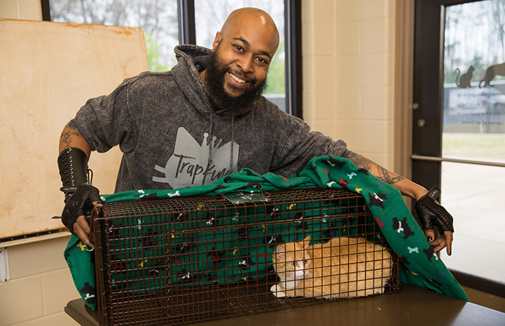 "Sterling ""Trap King"" Davis holding a live trap holding an orange and white cat"