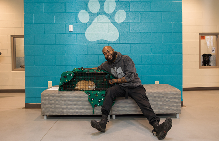 "Sterling ""Trap King"" Davis with a cat in a humane trap, sitting on a bench in front of a blue wall with a big paw print"