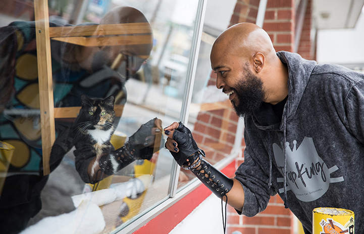 "Sterling ""Trap King"" Davis looking in a window at a calico cat"
