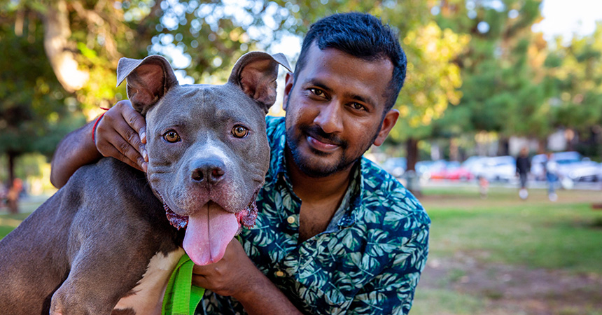 Man holding a smiling gray pit bull terrier whose tongue is out