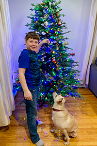 Young boy JP with Kash the dog in front of a decorated Christmas tree