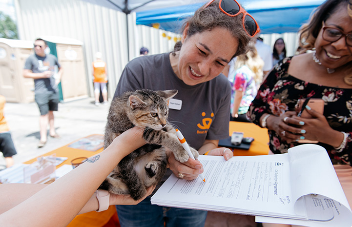 Volunteer Deyra Galvan smiling and helping complete some paperwork for a calico cat