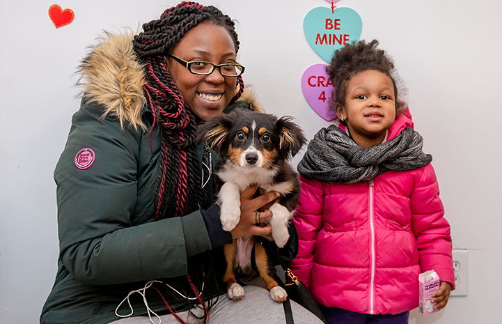 Woman and child who adopted a small fluffy dog, standing in front of Valentine's Day hearts at the adoption event