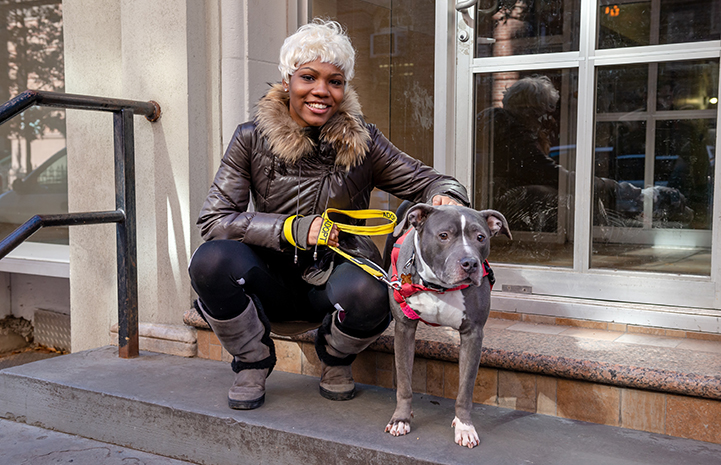 Woman on some steps next to the gray and white pit bull terrier she'd just adopted