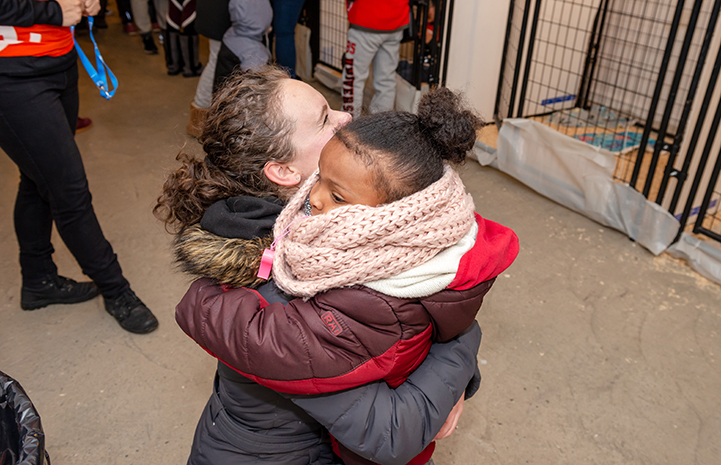A woman hugging a young girl at the Valentine's Day adoption event in New York City