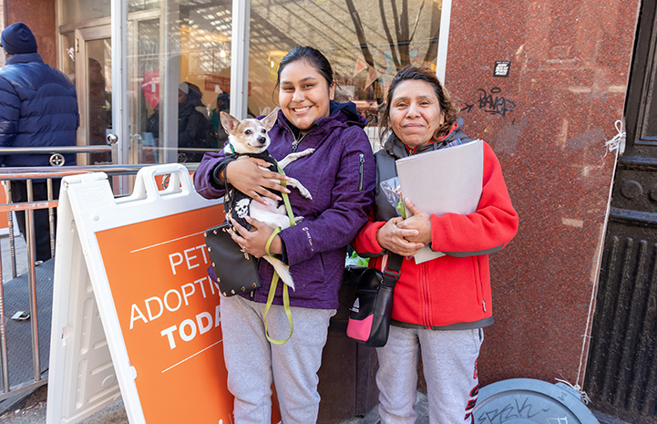 Two women holding a small dog at a New York Valentine's Day adoption event