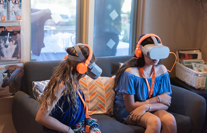Two women sitting on a couch wearing virtual reality headsets