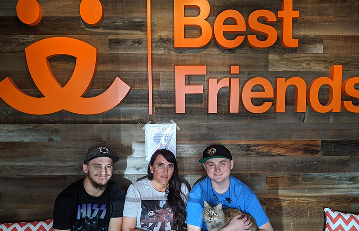 Boone the cat with his newly adopted family with a Best Friends sign and logo behind them
