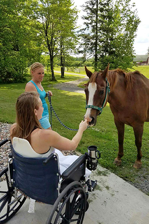 Volunteer Amber Kohnhorst making a friend at Horse Haven